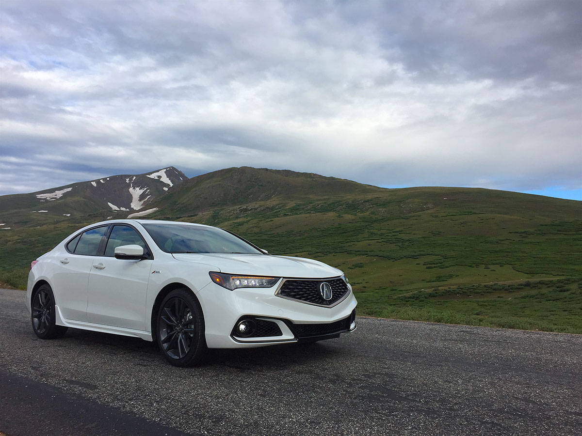 White Acura parked with a mountain showing in the background